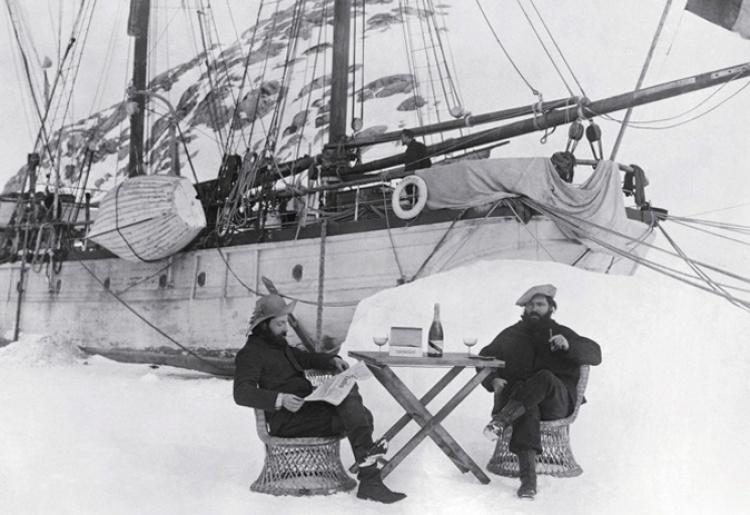 Le capitaine Charcot savoure une coupe de champagne, dans l'Antarctide