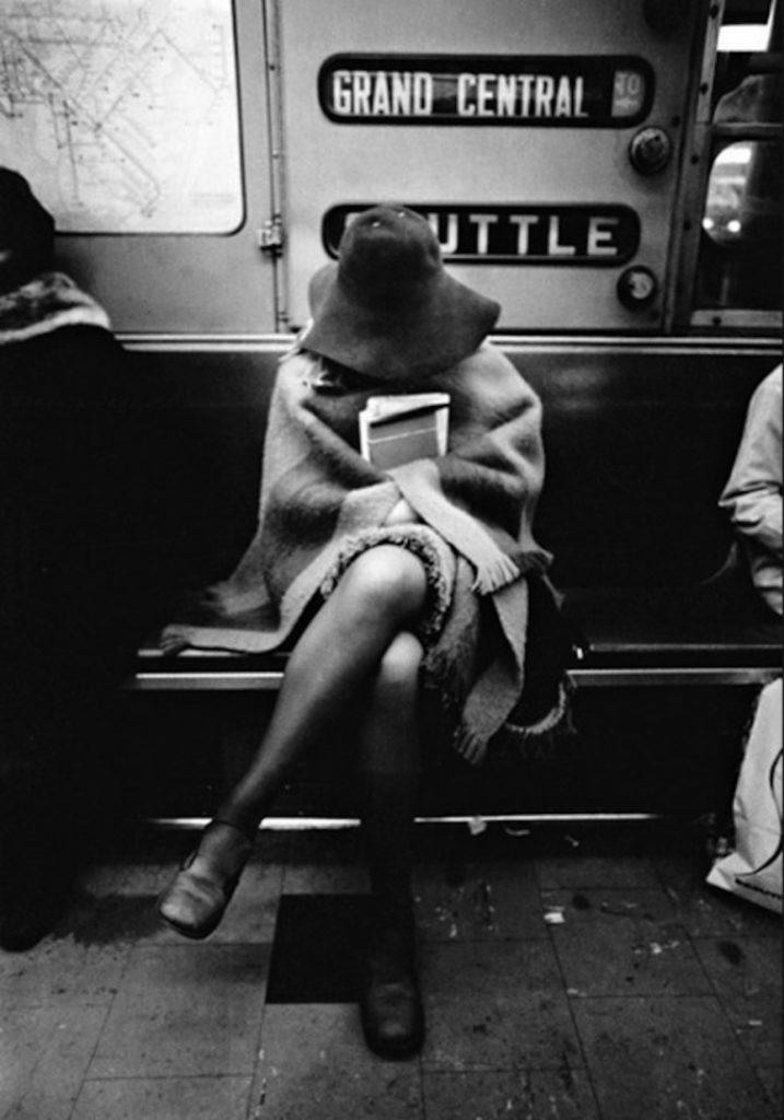 Une jeune fille, un chapeau sur la tête, un livre à la main. Dans le métro