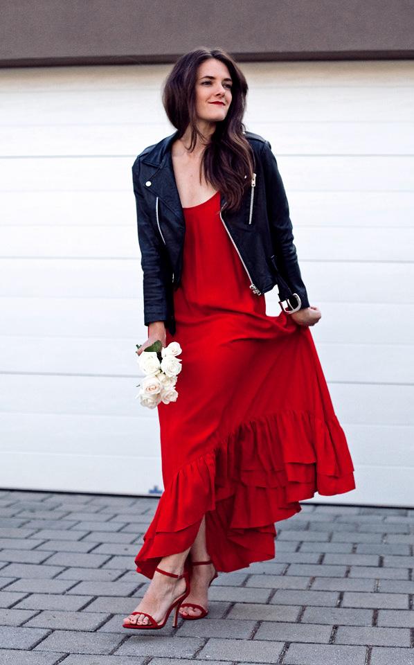 Robe longue rouge + blouson en cuir noir matelassé aux manches + escarpins rouges avec nœud noué autour de la cheville.