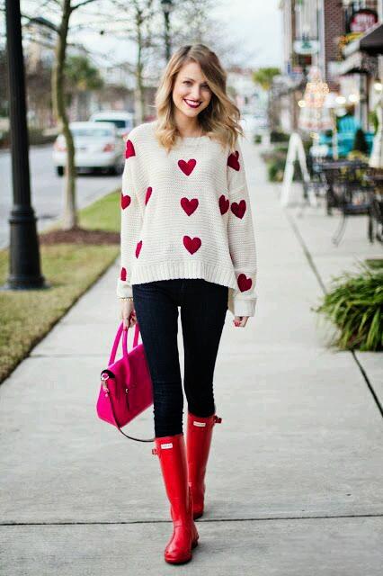 Tenue Saint valentin Casual : Pull blanc à motifs coeurs roses dans un style très girly + jean slim brut + bottes en caoutchouc rouges + sac rose.