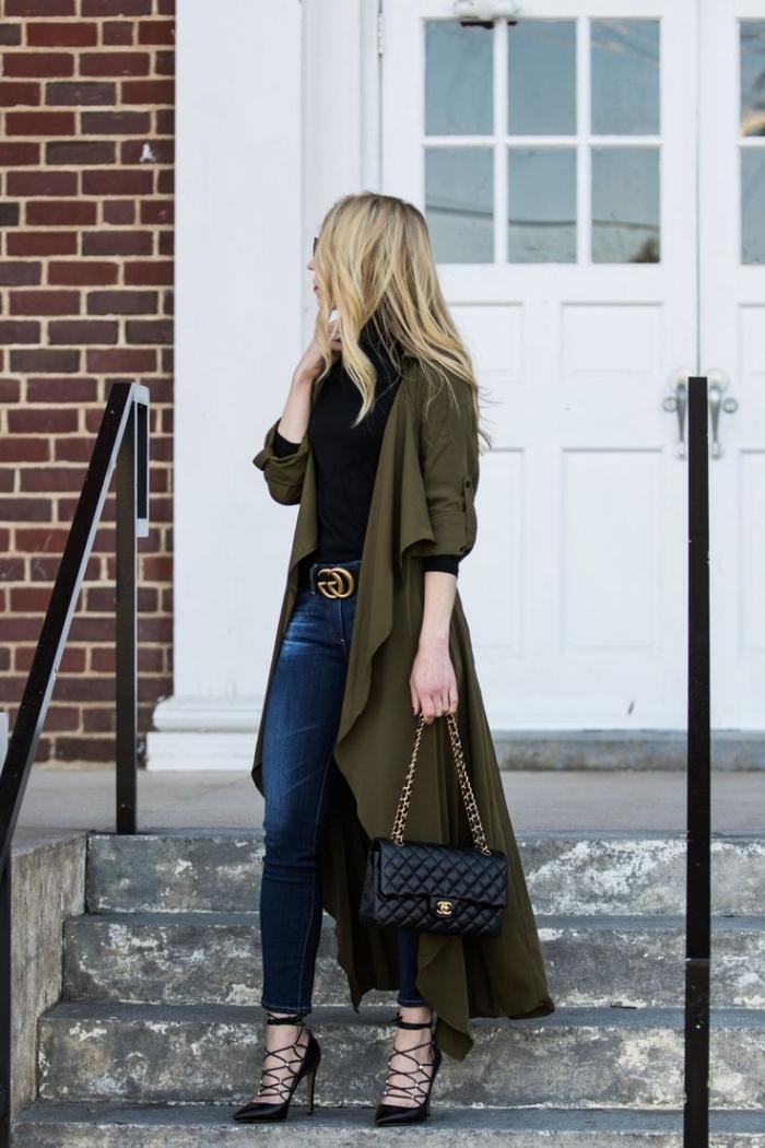 kaki couleur, femme élégante en jeans foncés et pull noir portés avec manteau long kaki foncé et chaussures noires