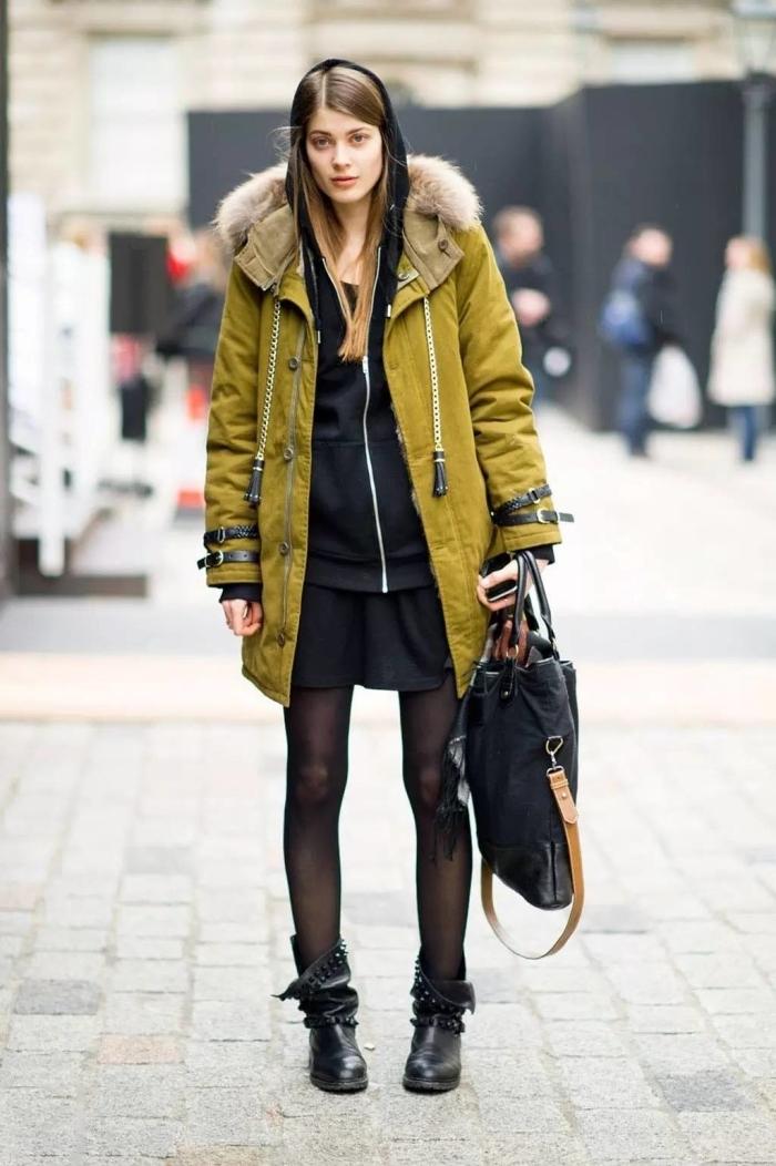 look veste kaki, jeune femme habillée en tunique noire et survêtement noir par dessus d'un manteau kaki à capuche en faux fur