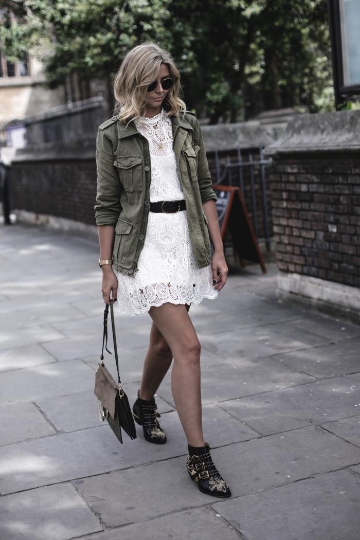 veste militaire femme, coupe de cheveux mi-longs avec coloration blonde de racines noires, robe blanche en dentelle portée avec ceinture en cuir noir
