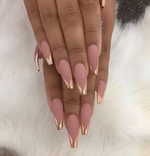 Rose avec des ongles en acrylique à pointe française dorée