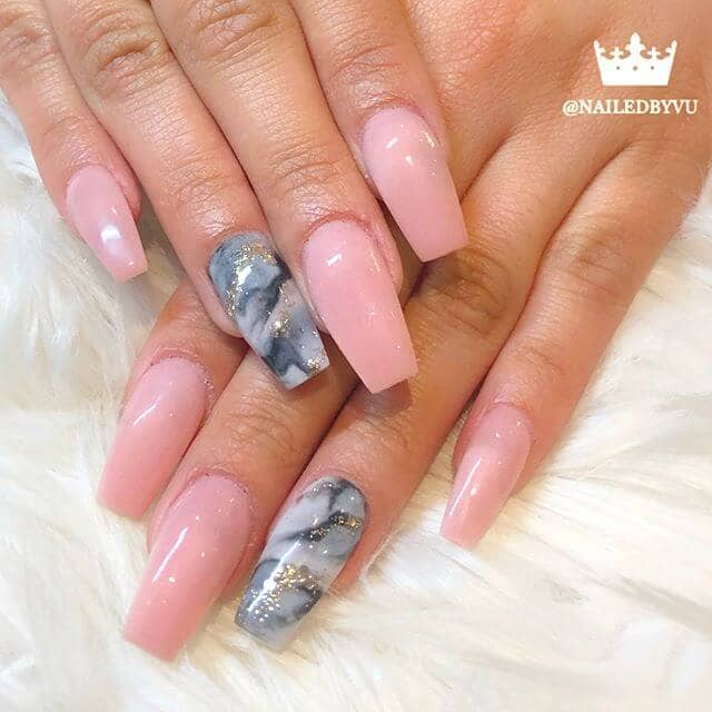 Manucure rose avec ongle marbré à l'accent de granit
