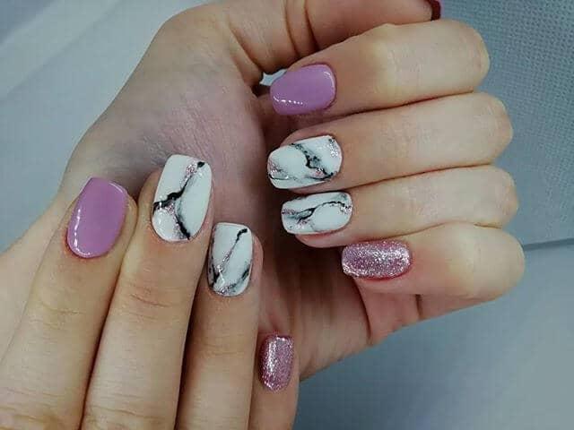 Design d'ongles avec accent marbré et paillettes roses