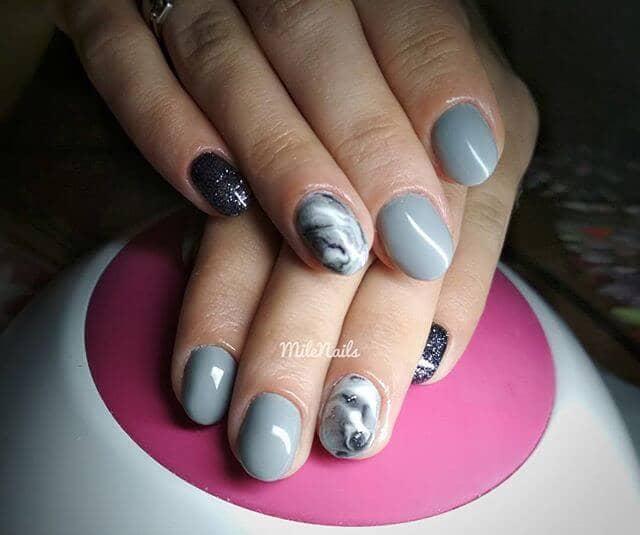 Manucure courte gris clair avec des paillettes de métal