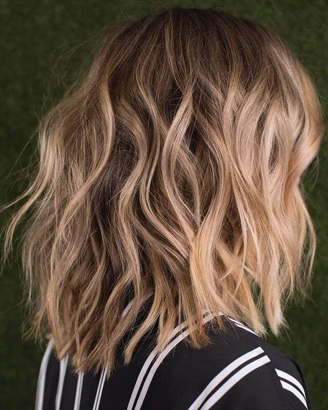 Cheveux bruns courts et ondulés avec des mèches