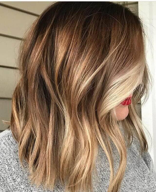 Le visage d'une blonde vanille est encadré par des cheveux courts