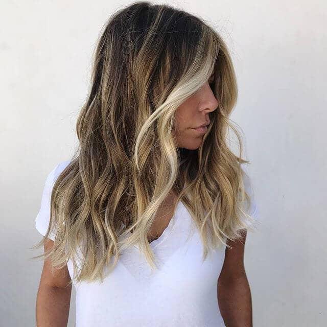 Cheveux blonds et bruns avec les points forts du cadrage du visage